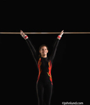 A hispanic female gymnast having just stuck a landing dismounting from the high bar and smiling in victory. Jet black background.